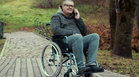 medicals : Disabled man talking on smartphone in wheelchair