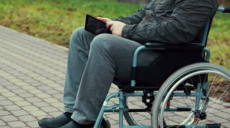 medicals : Disabled man with tablet PC in wheelchair