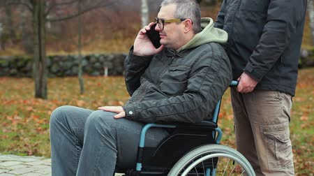 medicals : Disabled man talking on smartphone in wheelchair with assistant behind