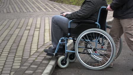 medicals : Assistant try pushing the wheelchair with disabled man on the pavement Stock Footage