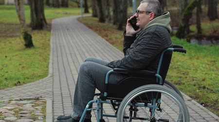 medicals : Disabled man in wheelchair on path talking on smartphone