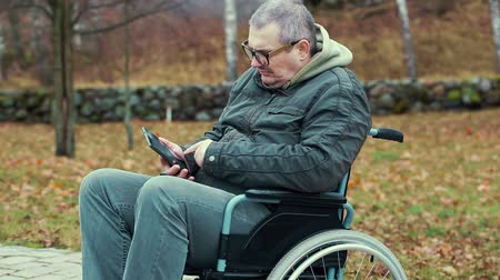 medicals : Disabled man in wheelchair on path using tablet PC Stock Footage