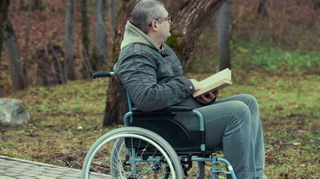 medicals : Disabled man reading book in wheelchair at outdoor