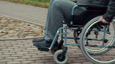 medicals : Disabled man using wheelchair on path Stock Footage