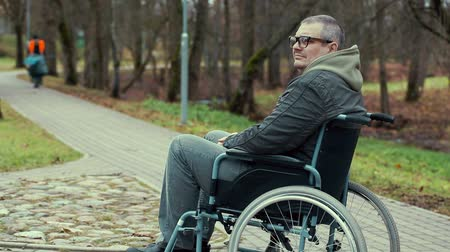 medicals : Disabled man in wheelchair waiting on path in the park Stock Footage