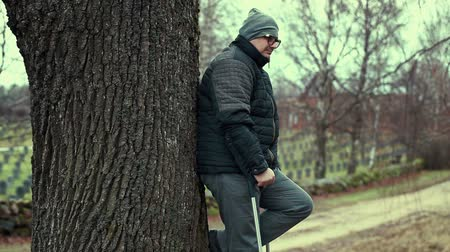 invalidita : Disabled man with crutches near tree