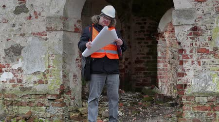 гражданский : Building inspector checking documentation at old ruins