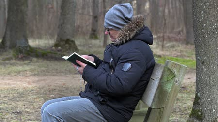 biblia : Man reading Bible and praying on bench in the park Stock mozgókép