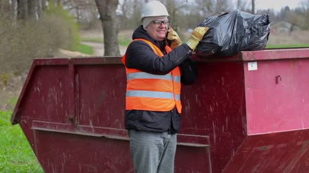 povinnost : Worker talking on smart phone and keeps garbage bag on waste container