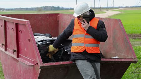 povinnost : Worker talking on smart phone near waste container