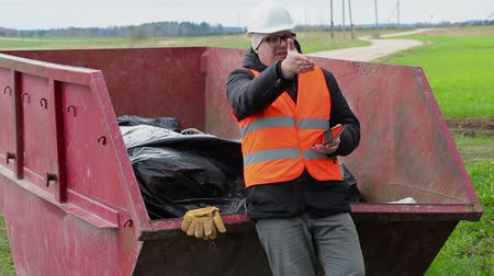 povinnost : Worker using tablet PC and talking near waste container Dostupné videozáznamy
