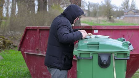 evsiz : Homeless find food and start eating near waste container Stok Video