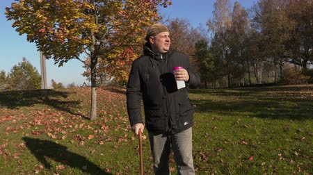 инвалидность : Man with cane drink coffee and walking in the park