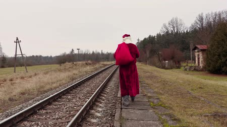 santa : Santa Claus with gift bag on platform near railway Stock Footage