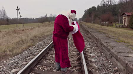santa : Santa Claus check gift bag on railway