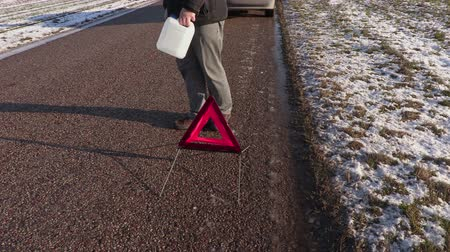 содействие : Man with empty can near warning triangle on the road