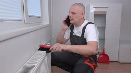 plumber : Plumber cleaning radiator and talking on phone