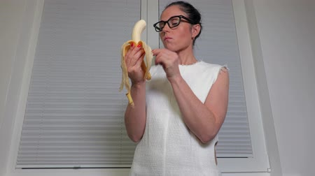 muz : Woman eating banana near window