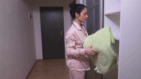 traje de passeio : Woman takes a towel from the closet