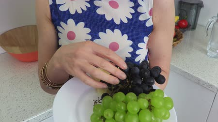 zdrowe odżywianie : Woman eats apple cloves and grapes.Vegetarian concept