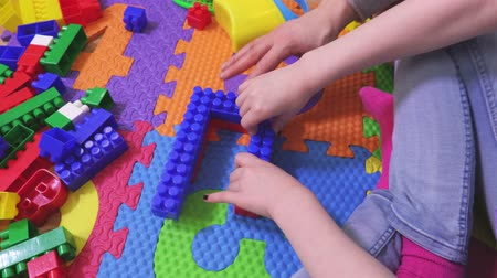 plaything : Mother help daughter fix toy bricks