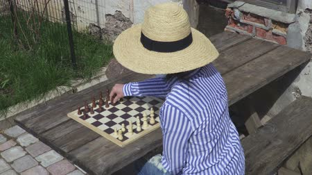 know : Woman playing chess outdoors Stock Footage