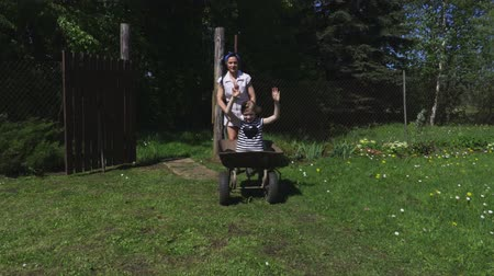 pushed : Little girl in a wheelbarrow pushed by a woman