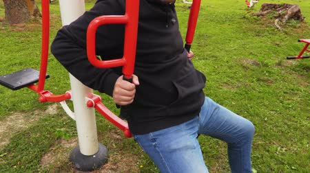 gym equipment : Man doing exercises on training machine in park