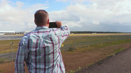 alma : Man take photos on smartphone near airport runway Stok Video