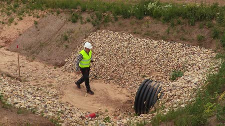 ditch : Engineer with walkie talkie near pipe in the deep ditch