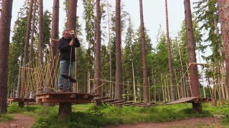 zip line : Man in rope course aerial park Stock Footage