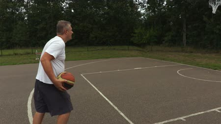 abroncs : Camera follows man with  basketball ball