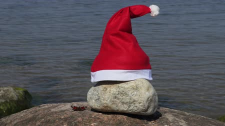 мотылек : Santas hat and colorful butterfly on the stone near sea