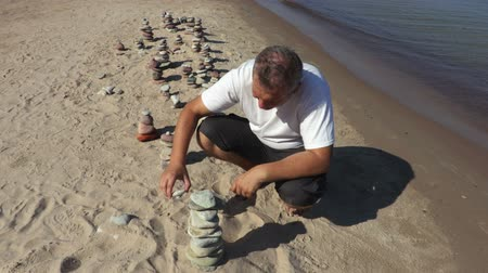 istikrar : Man builds balanced stone pyramid on the beach Stok Video