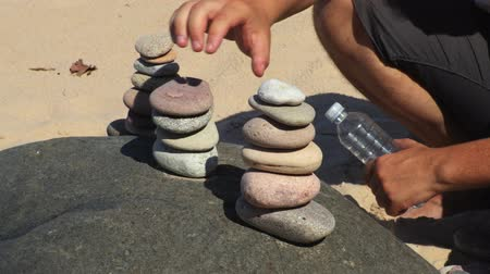 hierarchy : Man stacked stones at the beach close up Stock Footage