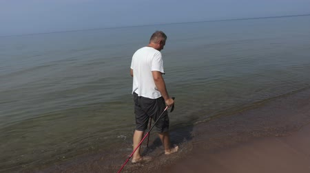 walkers : Man with walking poles slowly walk in the water Stock Footage
