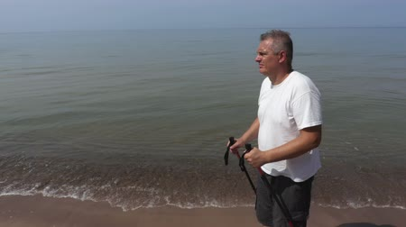 walkers : Man with walking poles slowly walk in the water in summer day