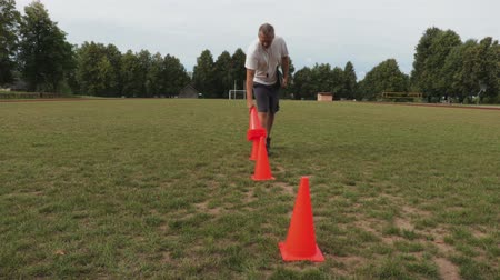 canto : Football coach collects the cones from the field Stock Footage