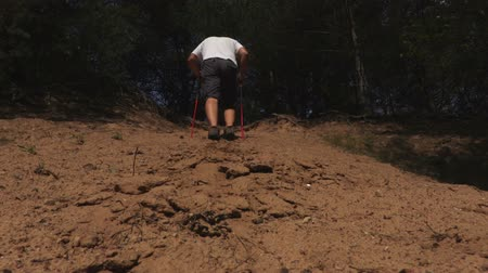 walkers : Hiker with walking poles climb a sandy slope
