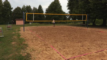 beach volleyball : Volleyball player serves across the net