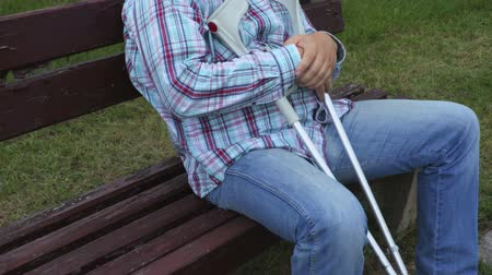 kule : Disabled man with crutches on bench