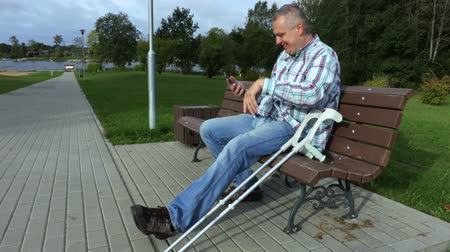 kule : Happy disabled man using smart phone