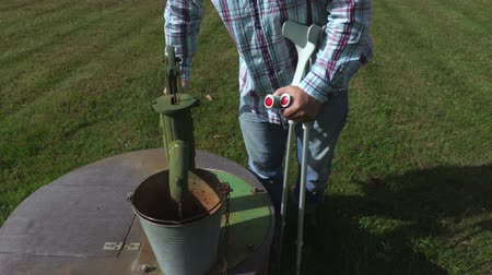 kule : Disabled man with crutches pumps water from the well