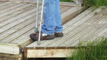 kule : Man with crutches on wooden bridge surface Wideo