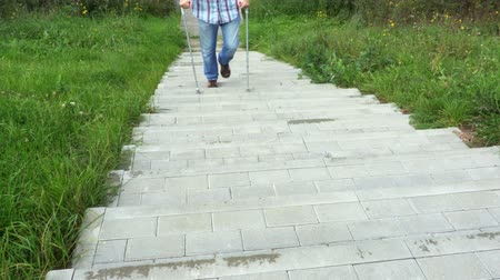 kule : Disabled man with crutches walking on footway Wideo