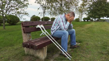 kule : Sad disabled with crutches in park on bench
