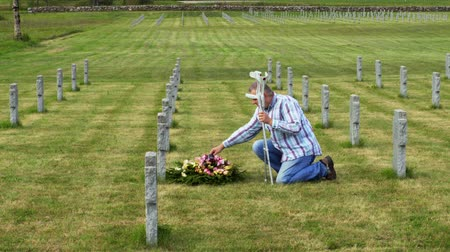 comemoração : Disabled veteran with crutches fix the flowers near to the grave