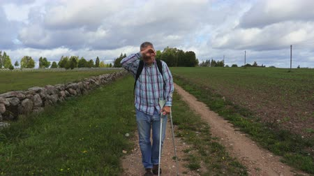 kule : Man with crutches comes down the road in autumn day