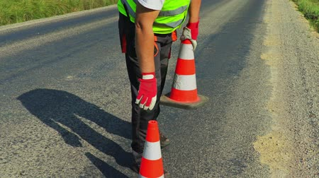 жесткий : Road construction worker with traffic cones on highway