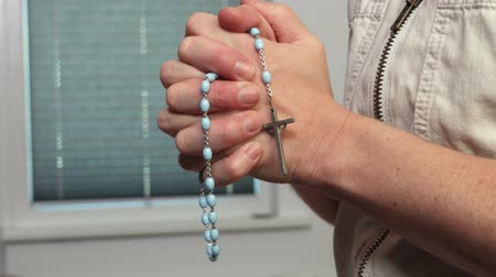 Womans hands with a crucifix